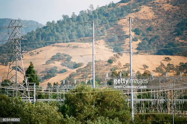 Electrical pylons and high tension wires are visible among hills at Clayton Substation an electrical distribution substation operated by utility...