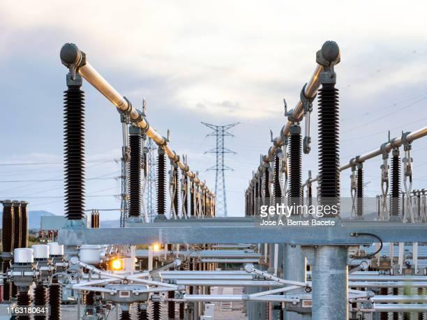 electrical transformer of high tension in a distribution electric power station of electricity power. - fornecimento de energia imagens e fotografias de stock