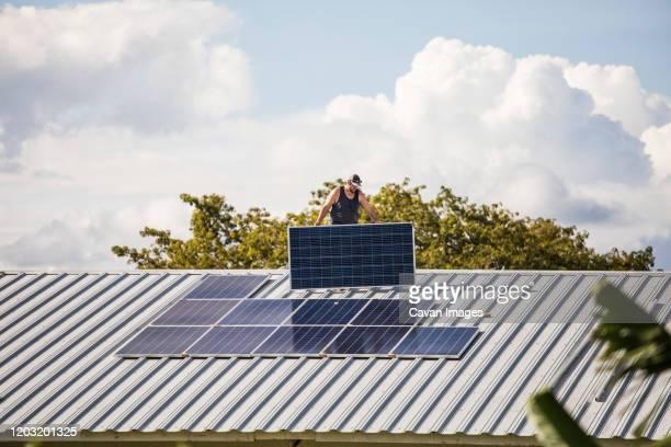 electrician carries solar panel on rooftop. - steuerpult stock-fotos und bilder