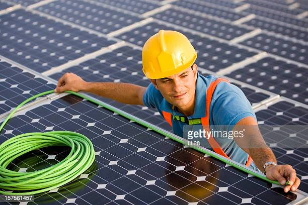 Electrician comparing a solar panel's width with a wire