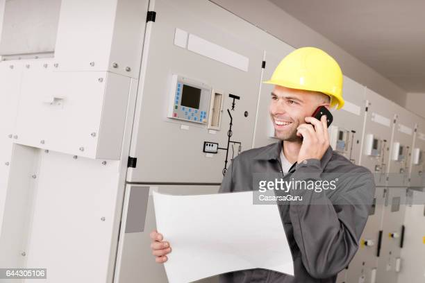 Electrician Consulting Experts Using Phone For Repairing Power Station