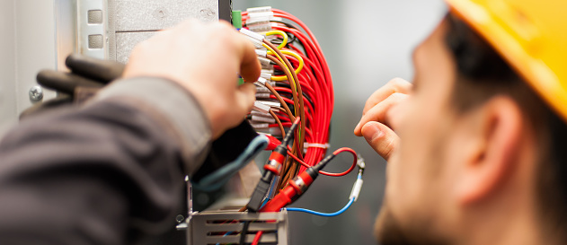Electrician engineer tests electrical installations on relay protection system 910235118