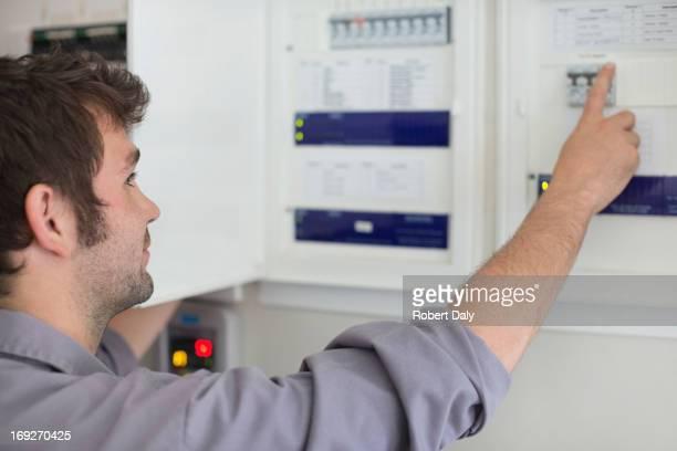 Electrician examining control panel