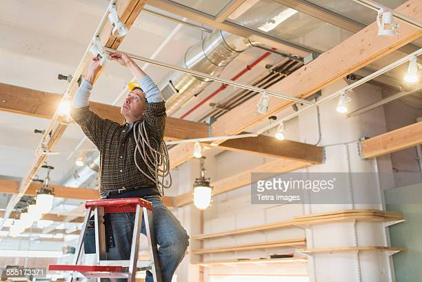 electrician fixing lightning equipment - electrician stock pictures, royalty-free photos & images