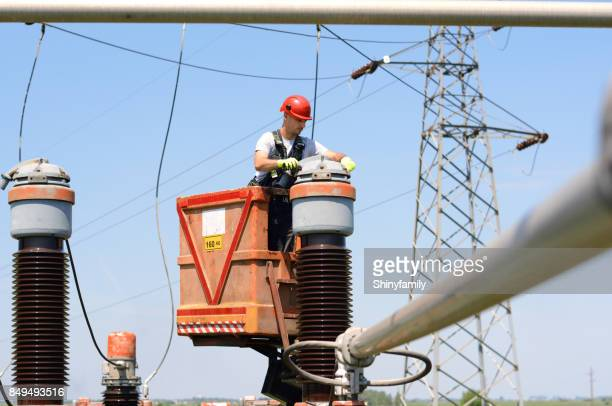 Electrician fixing power lines in power substation. Working in high.