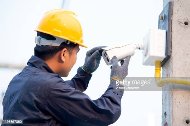 electrician fixing video surveillance camera outdoors. - business security camera stock pictures, royalty-free photos & images