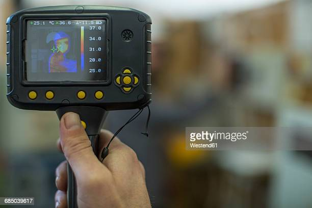 Electrician holding thermal imaging camera