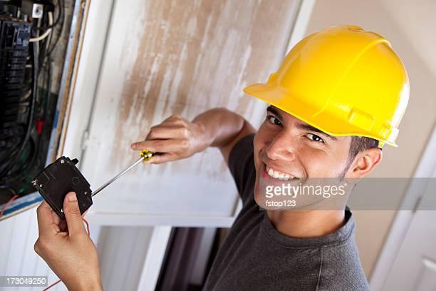 Electrician in hard hat working on circuit breaker