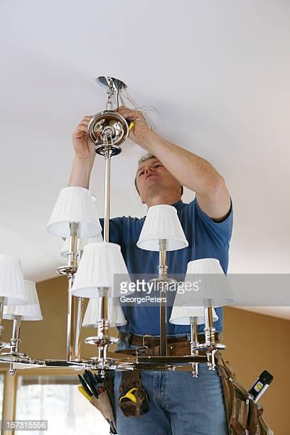Electrician Installing Designer Chandelier