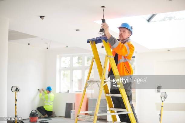 electrician installing downlights - electrician stock pictures, royalty-free photos & images