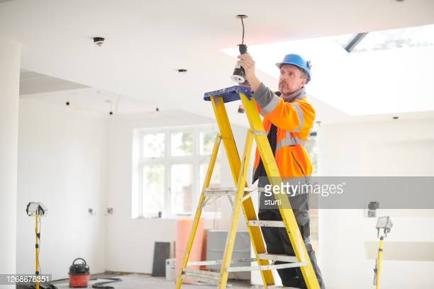 electrician installing downlights - ceiling stock pictures, royalty-free photos & images