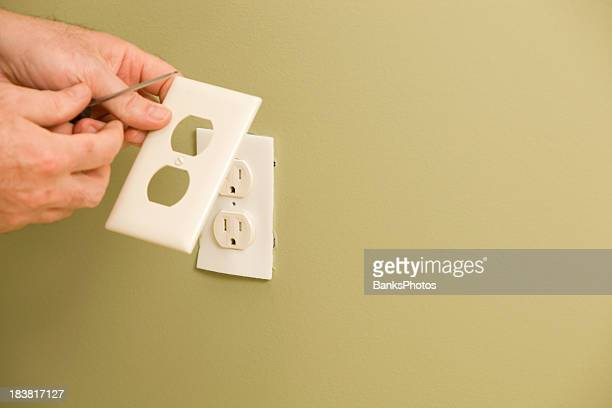 Electrician Installing Electric Outlet Insulation Pad