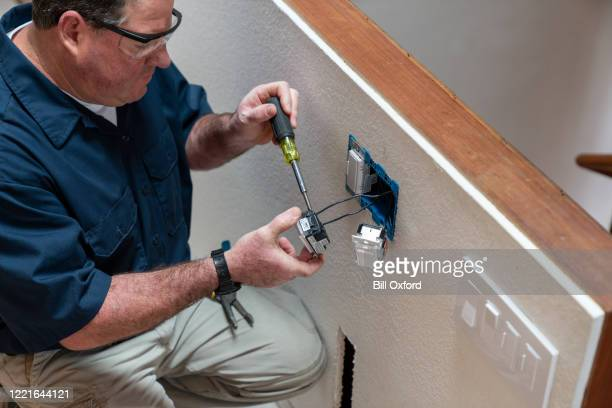 electrician installing light switch in home - electrical box stock pictures, royalty-free photos & images