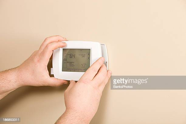 electrician installing new programmable thermostat - thermostat stock photos and pictures