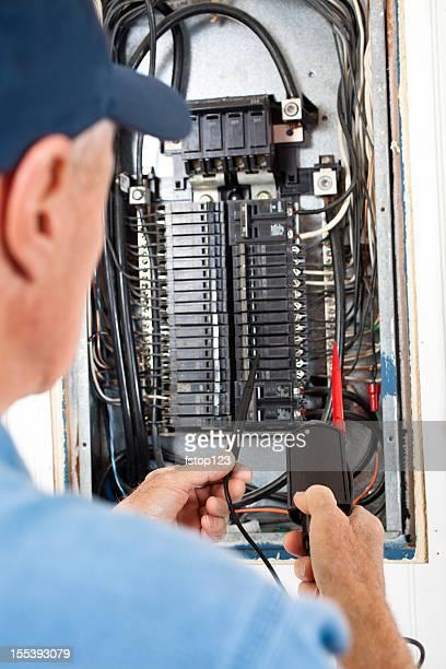 Electrician repairman doing electrical work in breaker box. Installing, repairing.