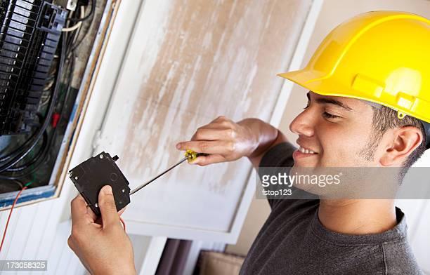 Eletricista de Empreiteiro de Reparações a fazer trabalho de disjuntor elétrico na caixa
