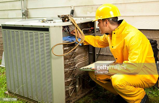 Electrician, repairman raincoat working on air conditioning unit outdoors.