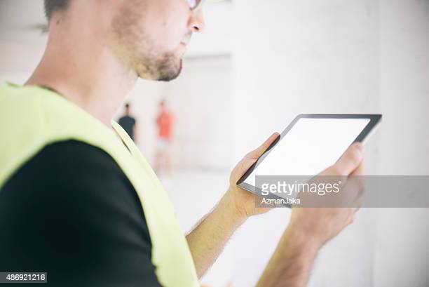 Electrician reviewing plans on digital tablet at construction site