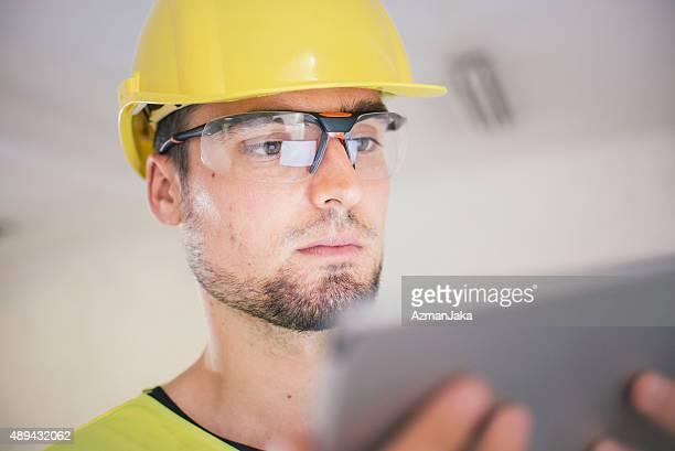Elektriker bei der Durchsicht der Pläne auf digitale tablet auf Baustelle
