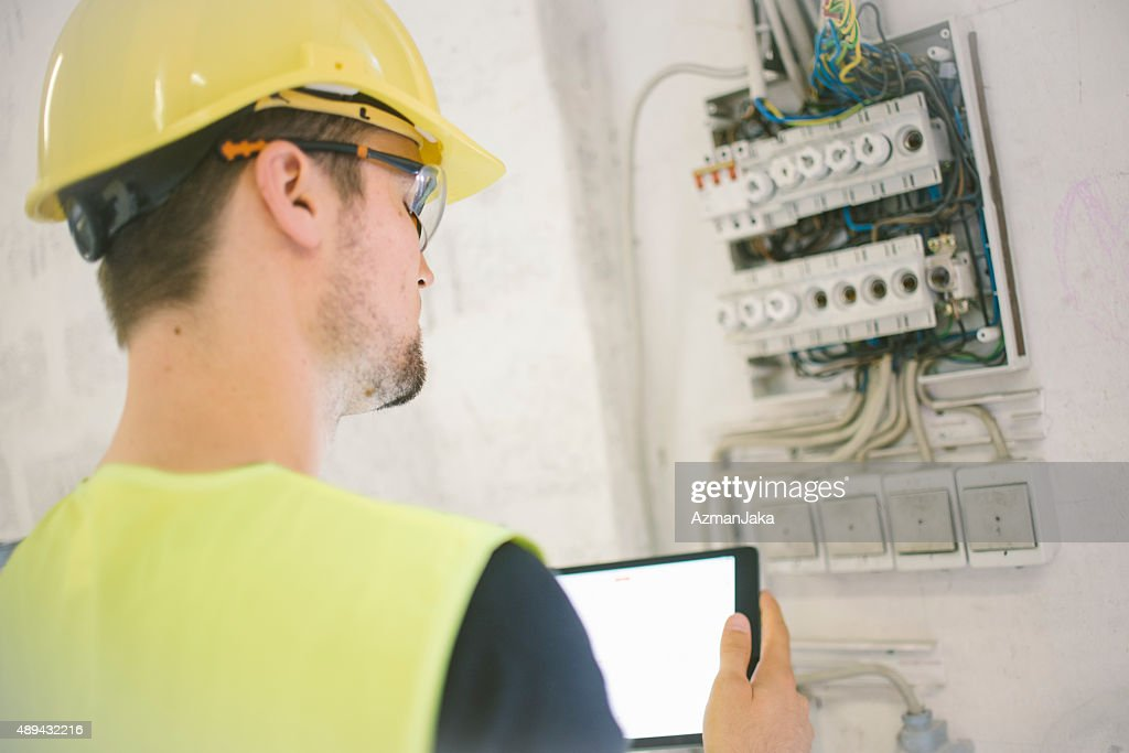 Electrician reviewing plans on digital tablet at construction site : Stock Photo