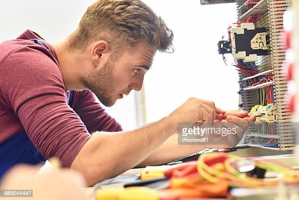 Electrician student working at electrical panel