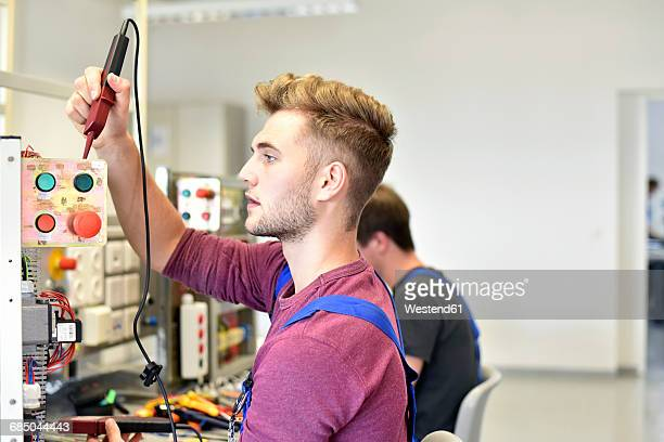Electrician students looking at device