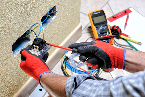 Electrician technician at work with safety equipment on a residential electrical system 937114374