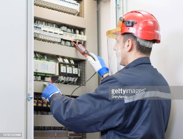electrician testing for voltage on terminal block - electrical box stock pictures, royalty-free photos & images