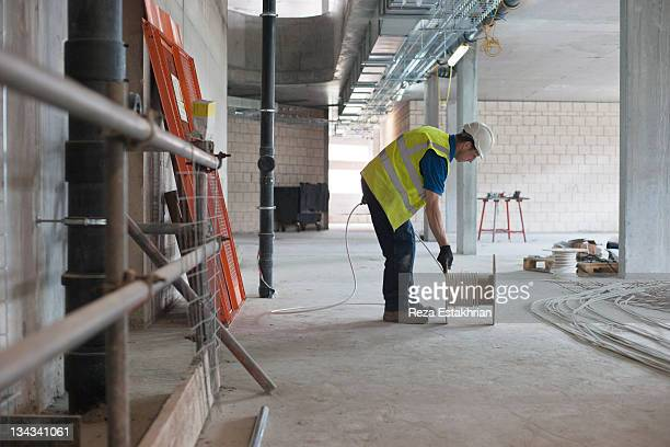 electrician unwinds electrical cable - construction industry stock pictures, royalty-free photos & images