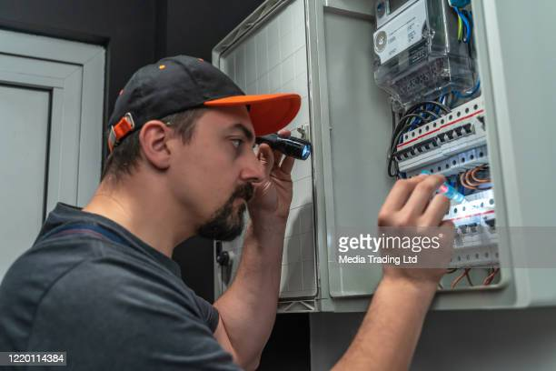 electrician use flashlight to repair fuse box - electrical panel box stock pictures, royalty-free photos & images