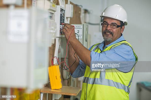 Electrician using voltmeter