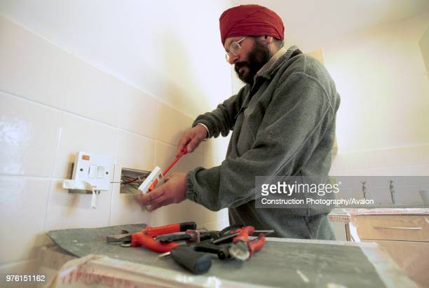 Electrician wiring a socket Council Houses refurbishment London