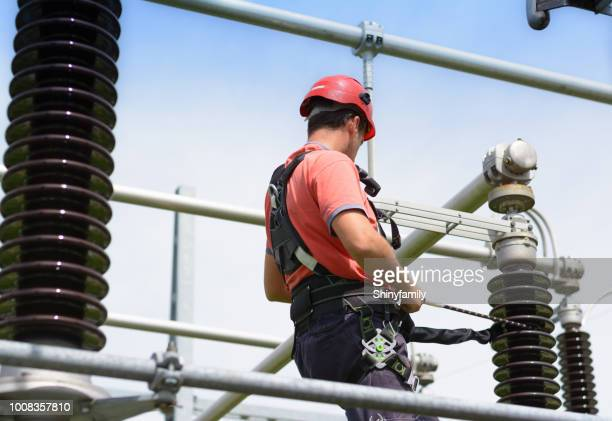 electrician with protective workwear, hardhat and safety harness at work - safety harness stock photos and pictures