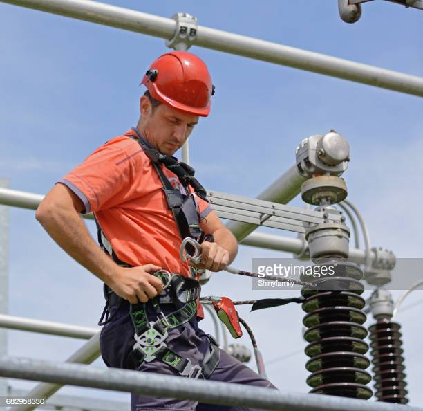 electrician with protective workwear, hardhat and safety harness working - high up stock photos and pictures