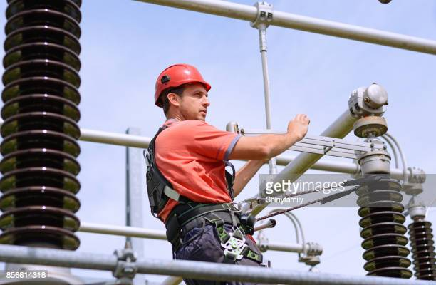 Electrician with protective workwear, hardhat and safety harness working