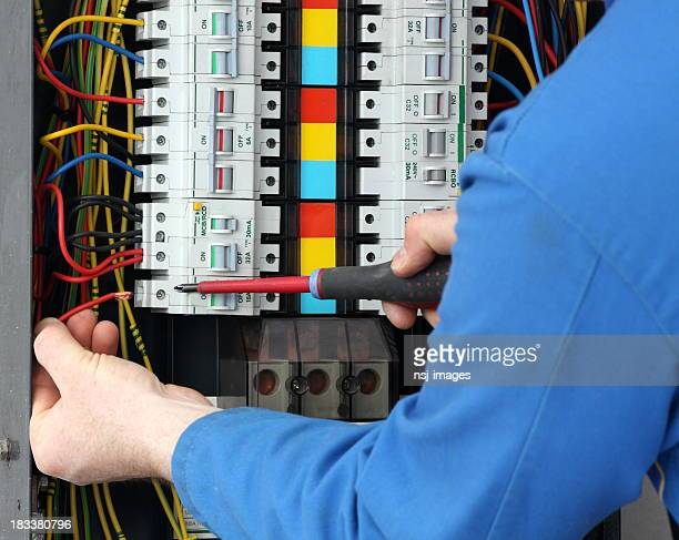 Electrician working at a fuse box.