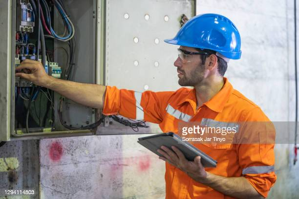 electrician working at circuit electrical panel. - electrical panel box stock pictures, royalty-free photos & images