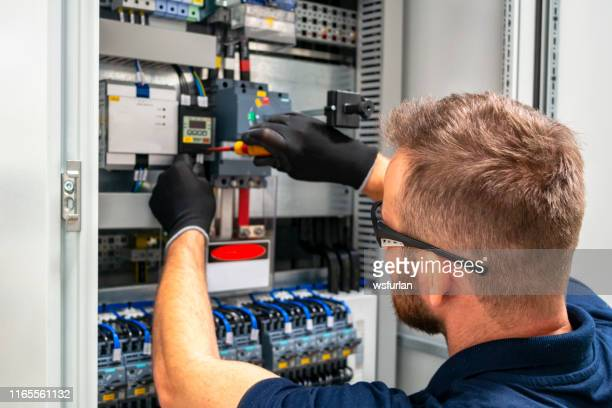 electrician working at electric panel - electricity stock pictures, royalty-free photos & images