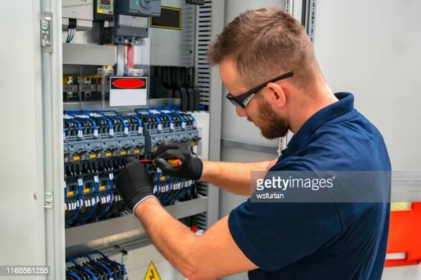 電気パネルで働く電気技師 - 人がつくり出したもの ストックフォトと画像