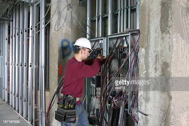 electrician working in an electrical panel. - electrician stock pictures, royalty-free photos & images