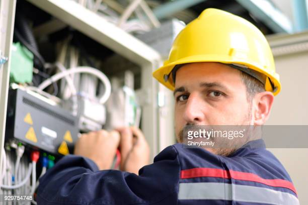 Electrician working on a circuit board in electric room.