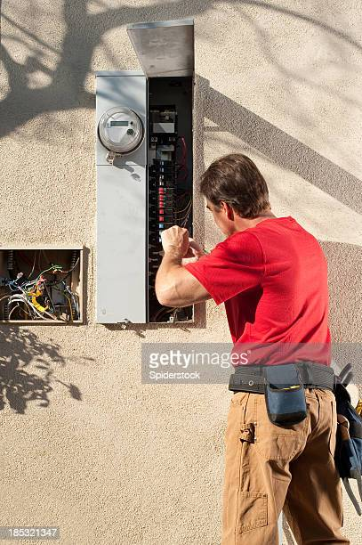 Electrician Working On Fuse Box