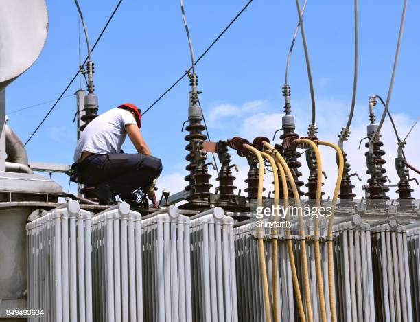 Electrician working on high voltage transformer in power station