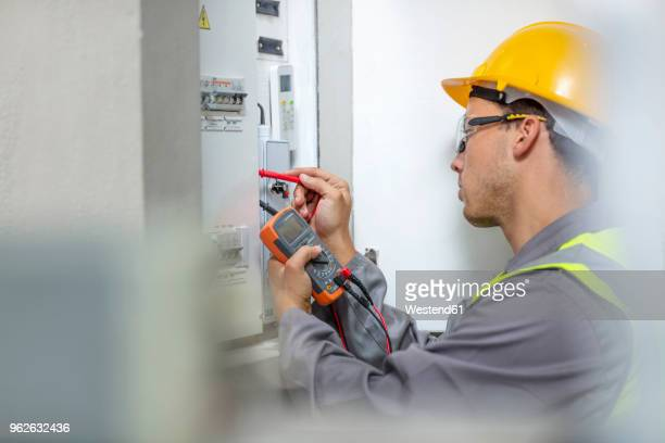 electrician working with voltmeter at fusebox - electrician stock pictures, royalty-free photos & images