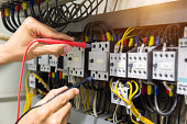 Electricians hands testing current  electric in control panel.