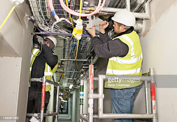 Electricians install cables
