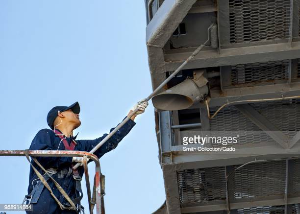 Electrician's Mate Fireman Joshua Broman painting the aircraft carrier USS George HW Bush Norfolk Virginia April 30 2018 Image courtesy Petty Officer...