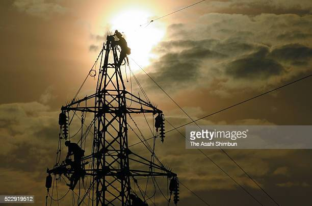 Electricians work on the highvoltage electrical power lines damaged by the earthquake on April 20 2016 in Minamiaso Kumamoto JapanAs of early morning...