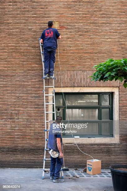 electricians working on a brick wall building facade - emreturanphoto stock pictures, royalty-free photos & images