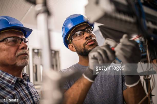 electricians working on a fuse box - protective eyewear stock pictures, royalty-free photos & images